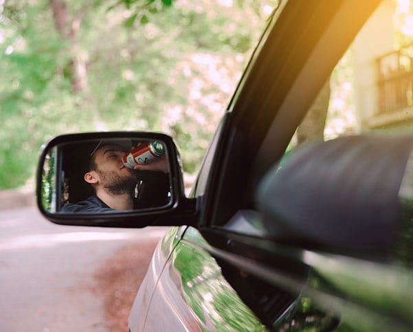Man drinking a canned drink while in a car